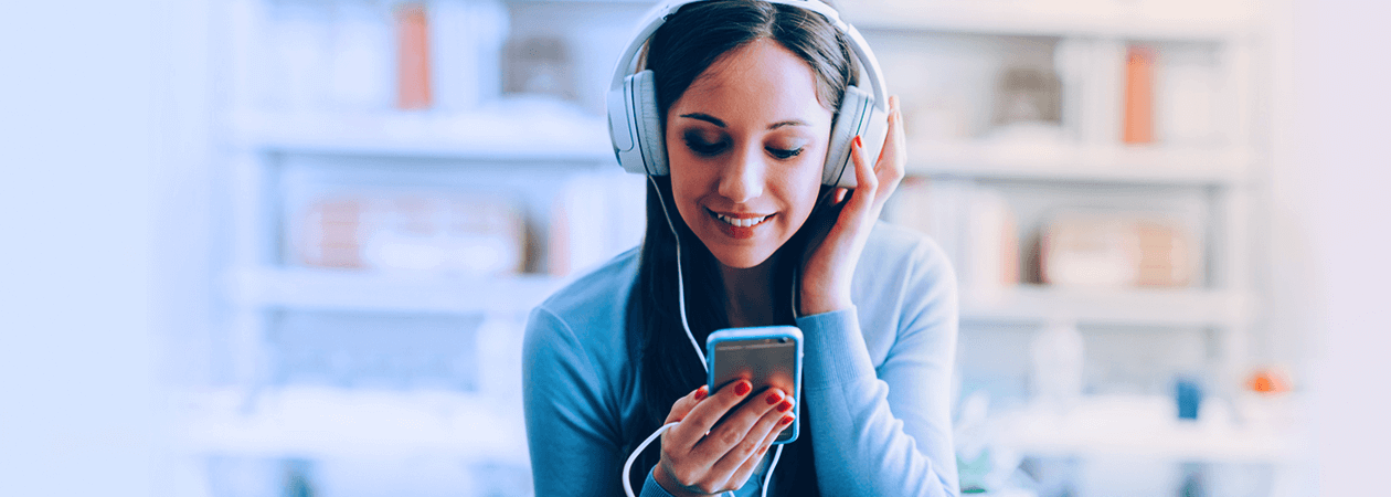 Mulher mexendo no celular com fones de ouvido