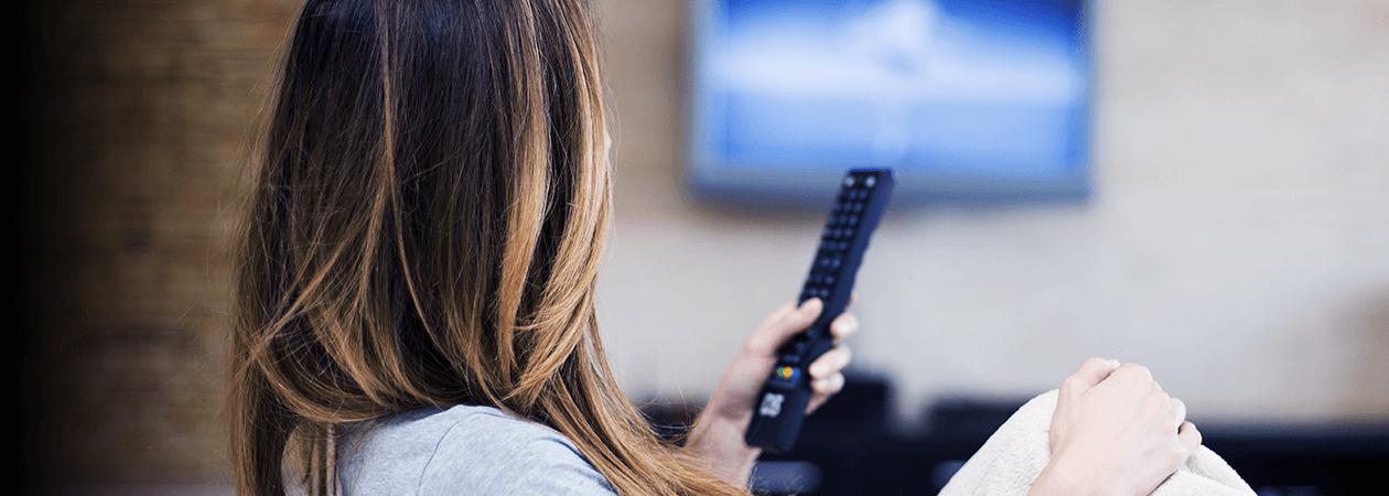 Mulher segurando controle remoto em frente a uma TV