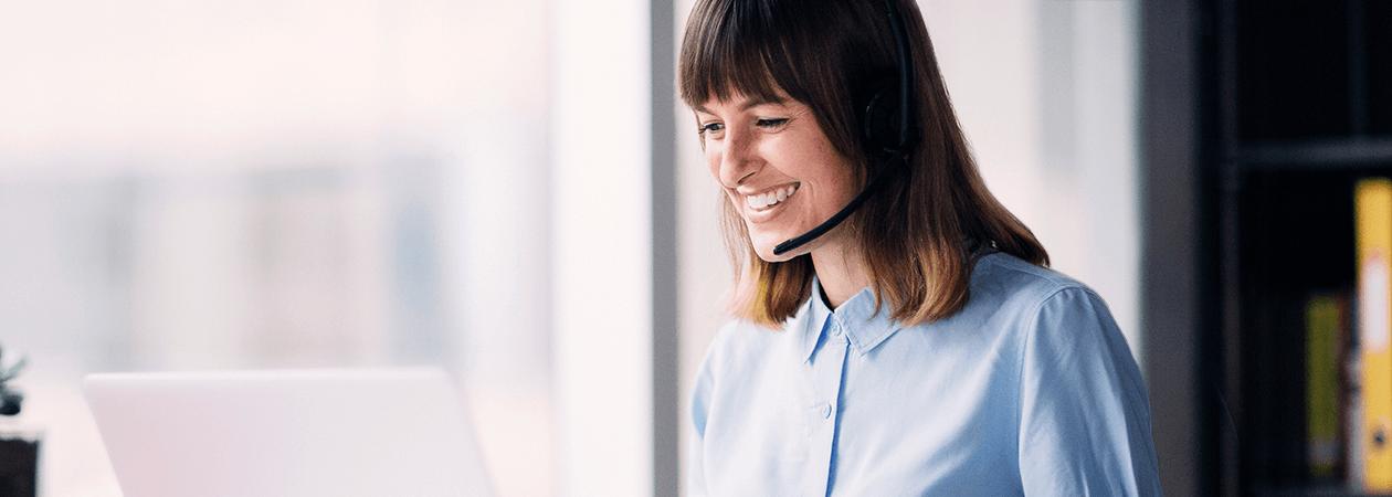 Mulher com fones de ouvido falando por chat de vídeo no computador