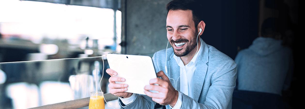 Homem sorrindo olhando para tablet e com fones de ouvido