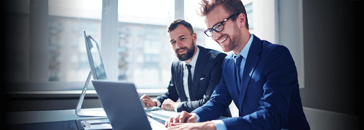 Empresários sentados um ao lado do outro enquanto estão mexendo em laptop