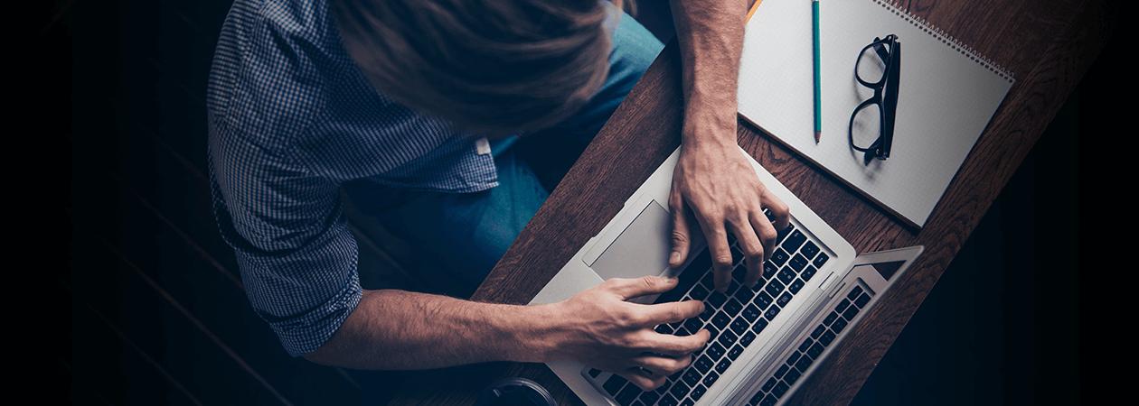 Homem digitando em laptop sentado à mesa ao lado de um caderno