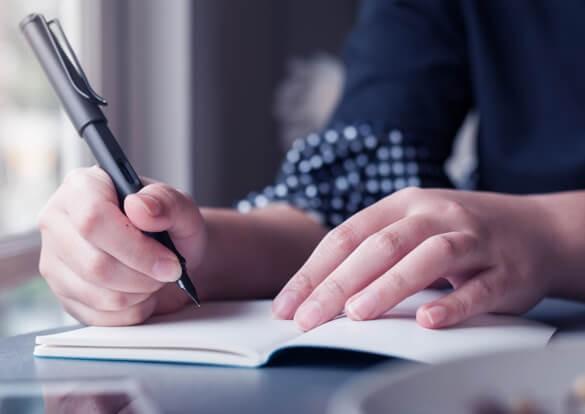 Estudante escrevendo em caderno com caneta